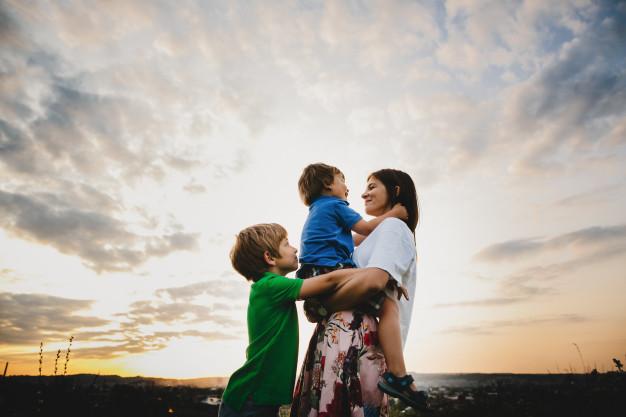 mama-abraza-sus-dos-pequenos-hijos-tiernos-pie-rayos_8353-8553