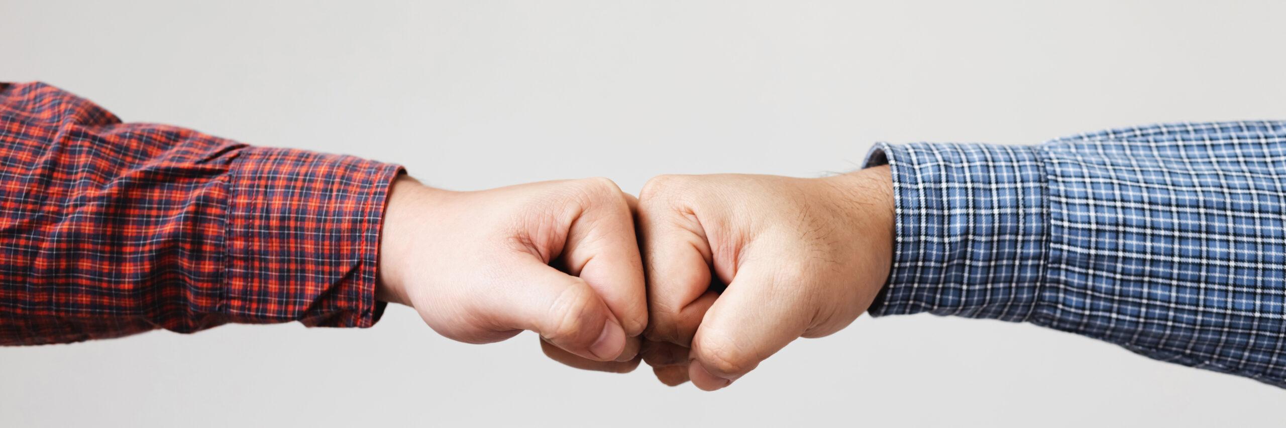 Closeup of arm wrestling or friendly handshake gesture.