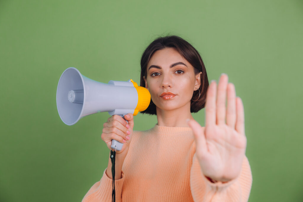 Young woman in casual peach sweater isolated on green olive color background unhappy serious with megaphone doing stop sing with palm of the hand. Warning expression